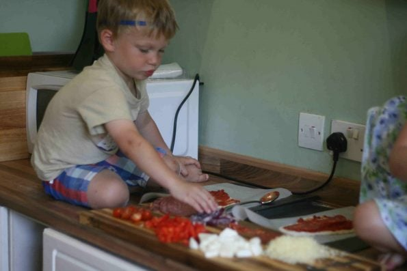 child making homemade pizza