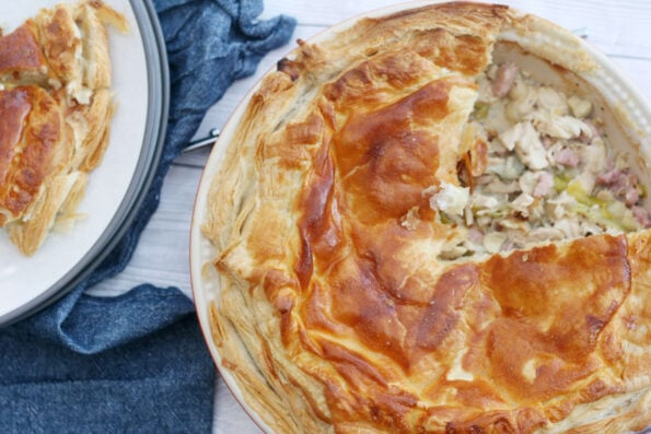chicken leek and mushroom pie shown from the top with a slice removed
