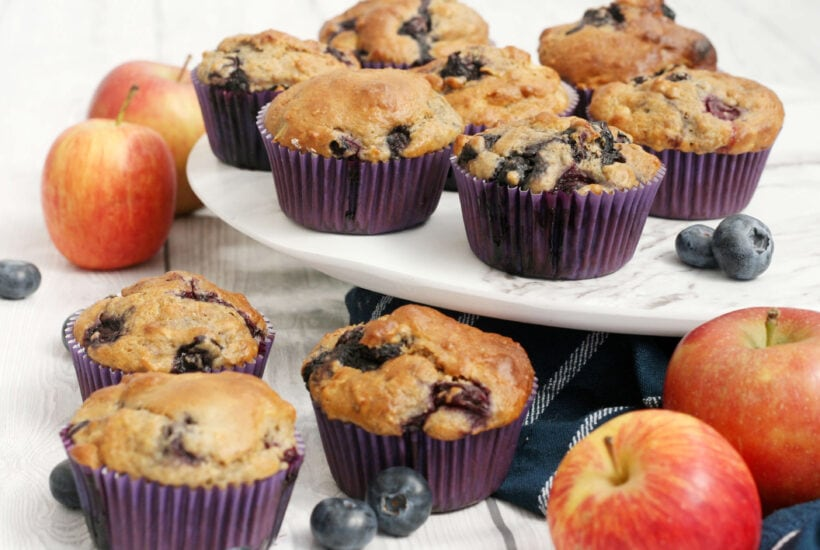 blueberry and apple muffins with apples and blueberries scattered around.