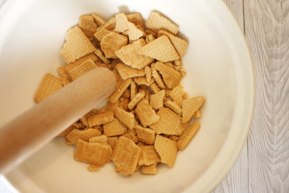 biscuits being crushed in a bowl with a wooden spoon