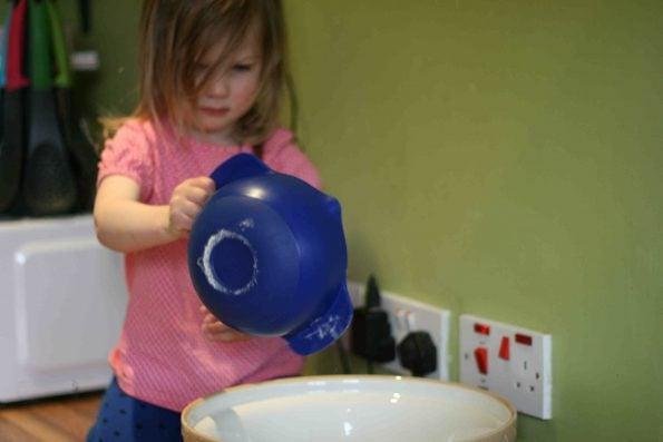 child adding flour to a bowl
