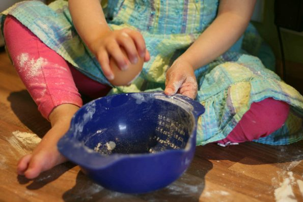 child cracking an egg into a blue bowl