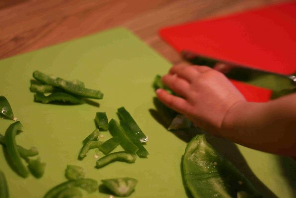 child cutting green peppers on a chopping board