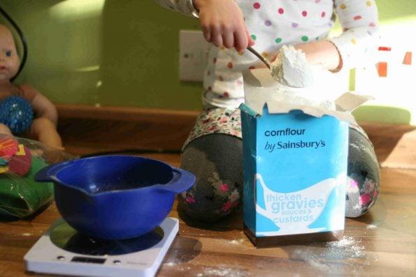 child weighing cornflour for shortbread