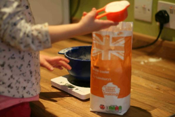 child measuring sugar.