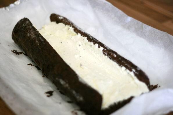 filling a yule log sponge with cream.