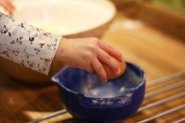 child cracking an egg.