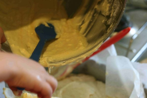 pouring lemon drizzle batter into a loaf tin