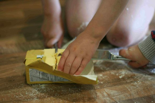 child cutting into a block of butter