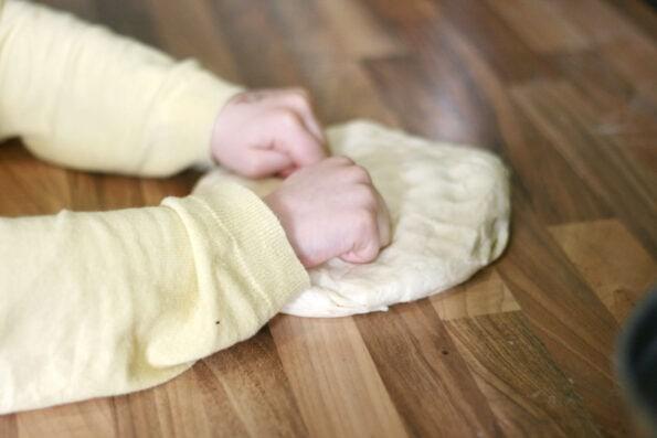 child knocking back dough