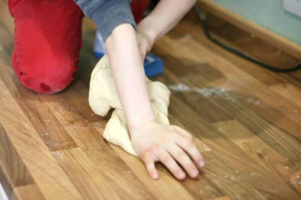 child kneading dough
