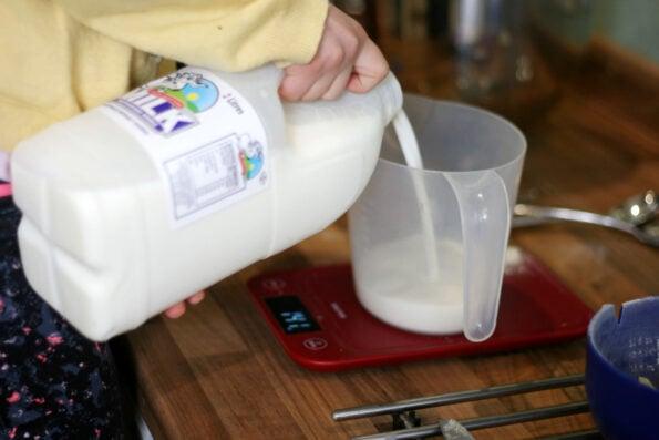 child measuring milk into a jug