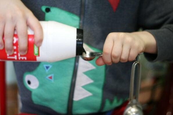 child measuring salt