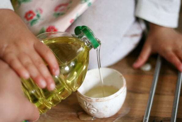 child pouring oil into a measuring cup