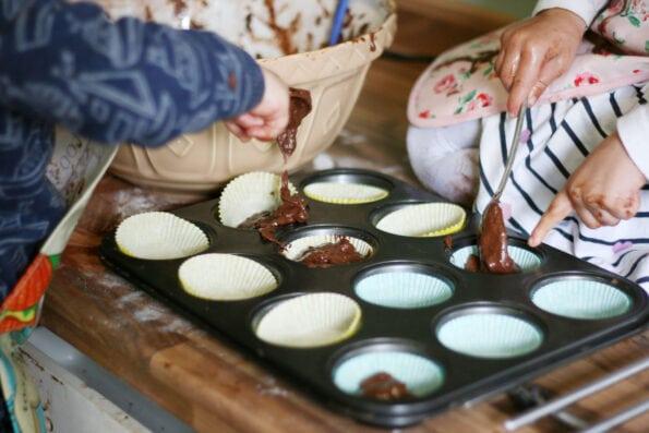 children adding chocolate muffin batter to a muffin tin