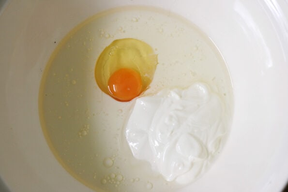yogurt, oil and an egg in a bowl