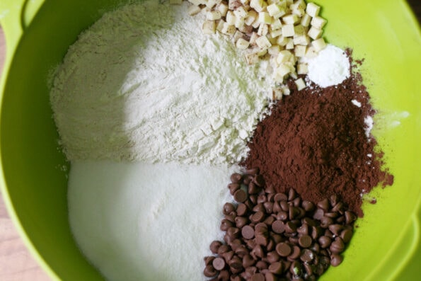 flour, sugar, chocolate chips and cocoa powder in a green bowl