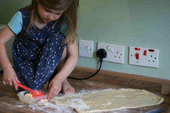 spreading butter on cinnamon roll dough.