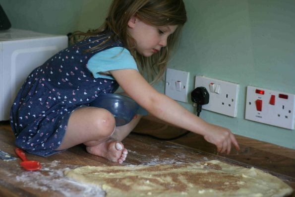 child sprinkling cinnamon sugar on cinnamon roll dough.