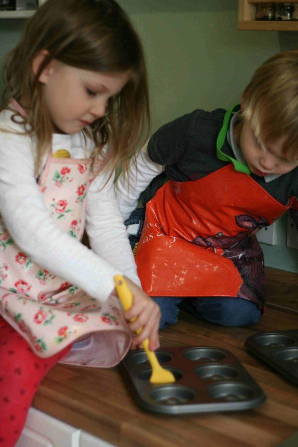 kids oiling a doughnut pan