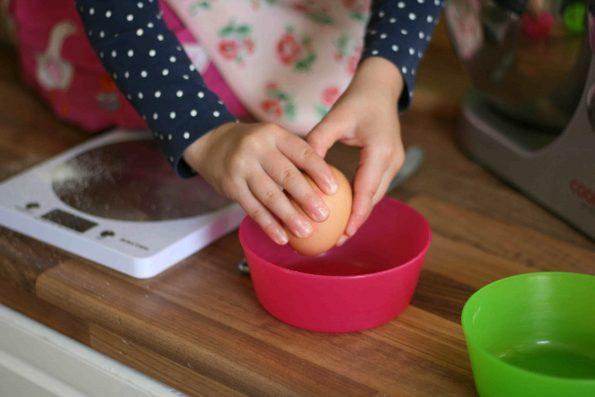 child cracking egg