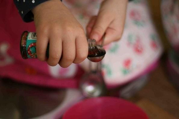 child measuring vanilla extract