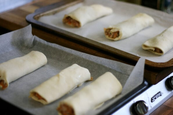 sausage rolls on a baking tray before being baked.