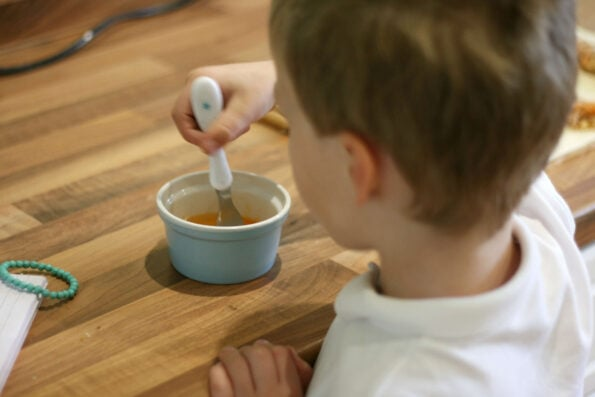 child whisking egg with a fork.