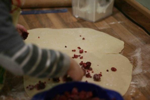 sprinkling raspberries on dough to make raspberry sweet rolls