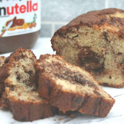 Banana and chocolate loaf sliced with a jar of nutella in the background