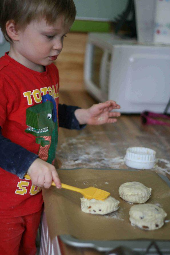 boy brushing milk on fruit scone recipe