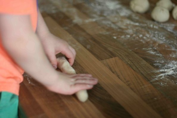 child rolling breadsticks