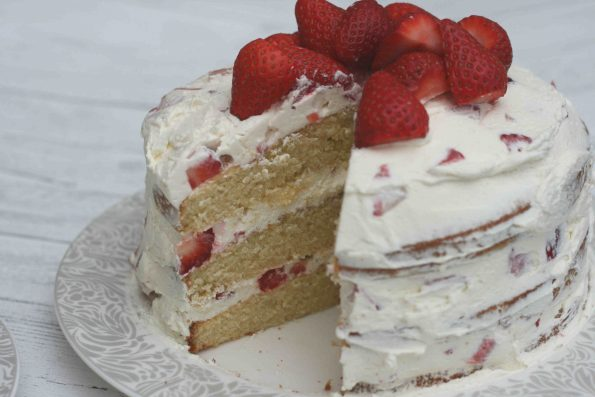 close up of strawberry cake with a slice cut out