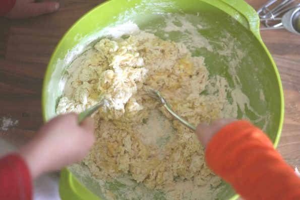 Child mixing flour and eggs to make pasta