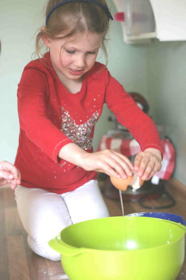Child cracking eggs into a green bowl