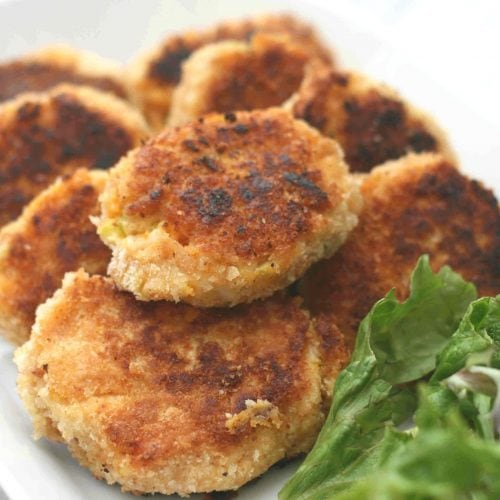sweet potato fish cakes on a white plate with salad.