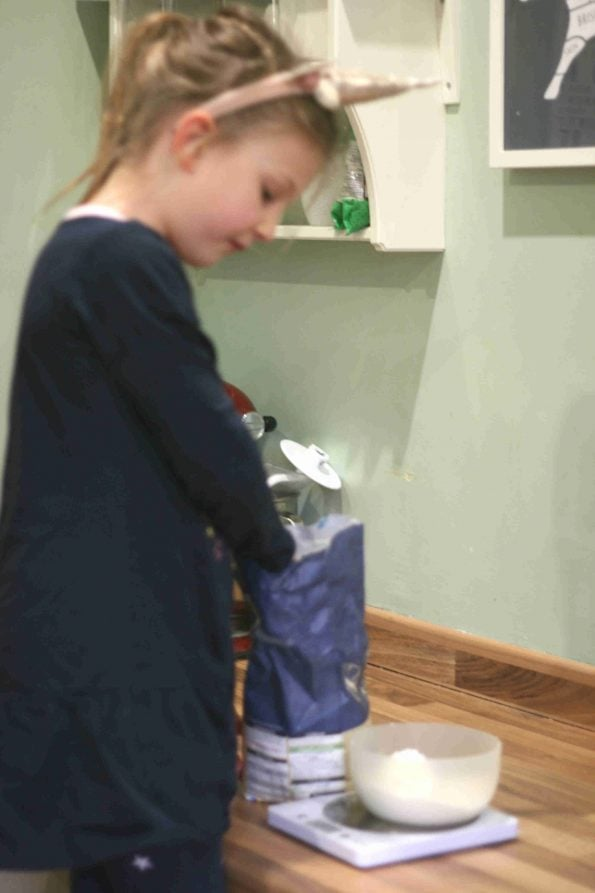 child measuring flour