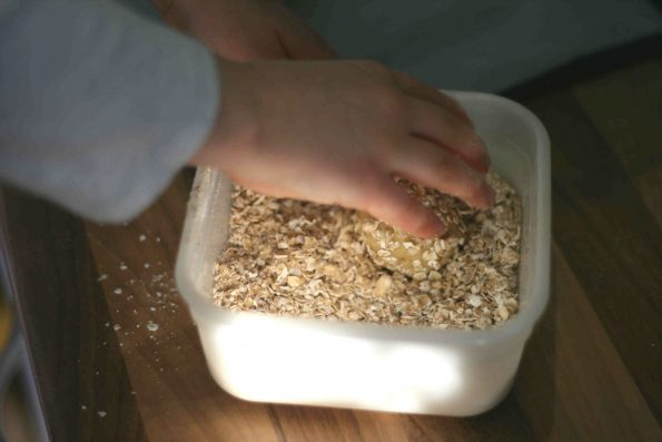 rolling biscuit dough in oats to make melting moments