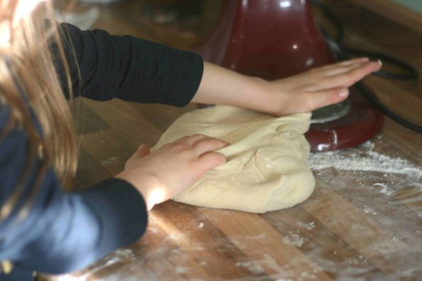 child kneading bun dough