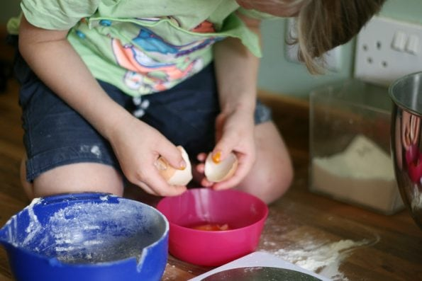 young child cracking an egg into a bowl