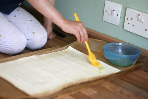 brushing melted butter on puff pastry