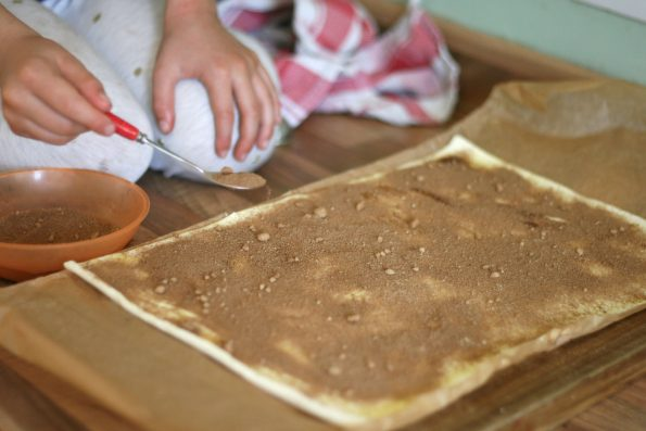sprinkling cinnamon sugar on pastry