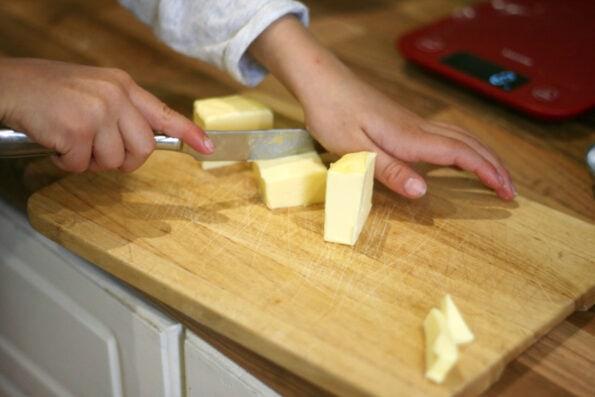 child chopping butter.
