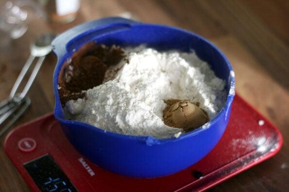 measuring flour in a blue bowl.