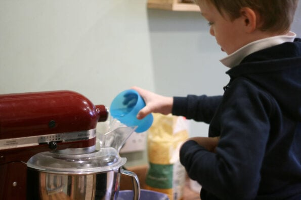 child pouring water into a mixer.