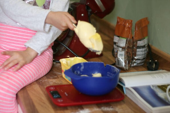 child measuring butter.
