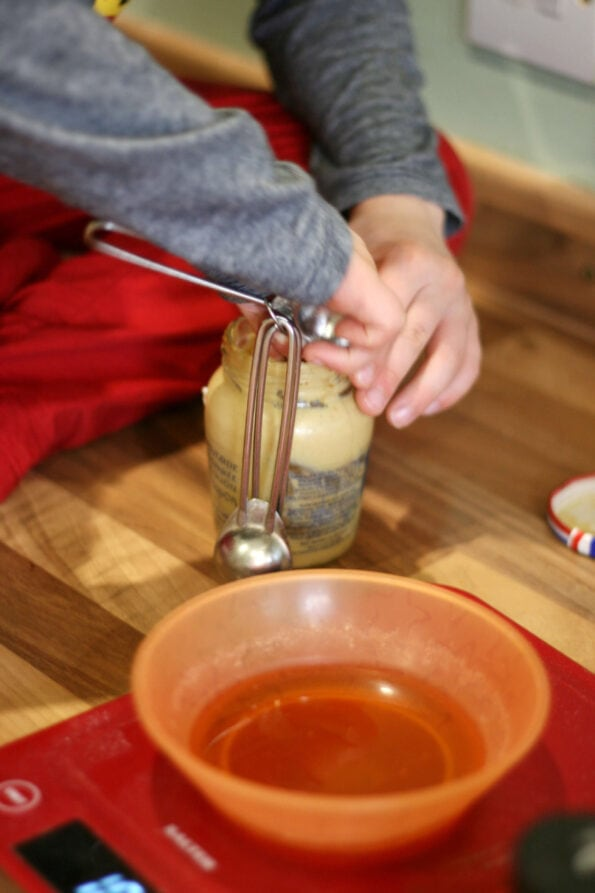 child measuring mustard.