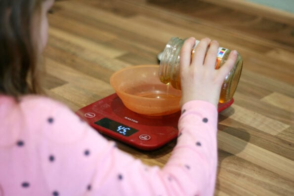 child measuring honey.