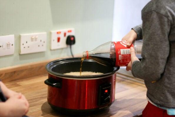 pour coke into a slow cooker.