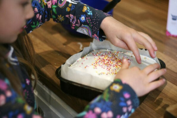 child adding sprinkles to a cake